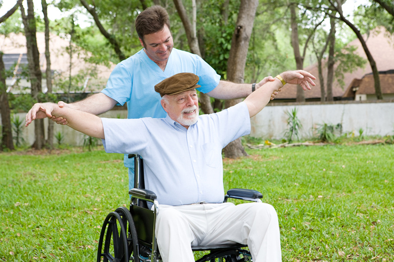 Disabled senior man does stretching exercise with the help of his physical therapist.