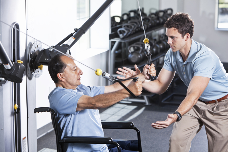 Physical therapist helping wheelchair bound senior Hispanic man (60s), exercising upper extremities.